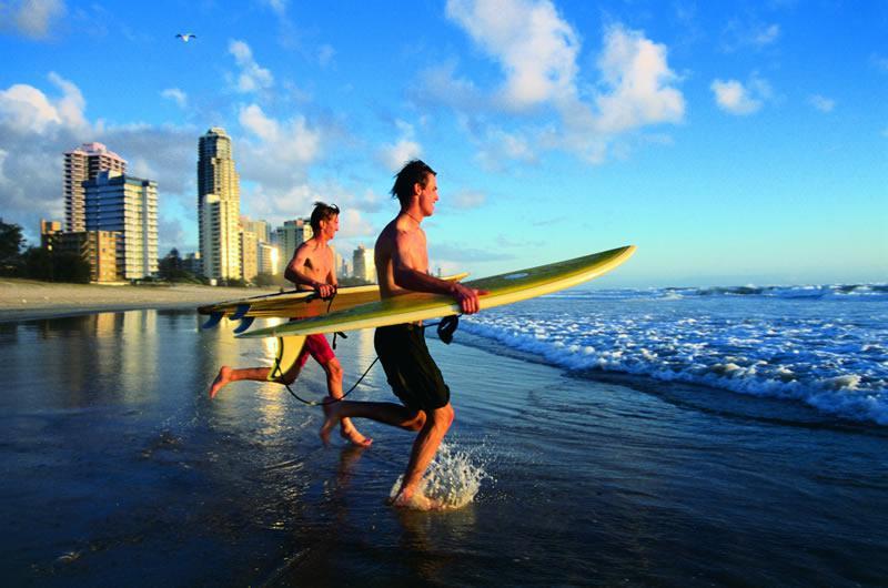 Deux hommes qui s'élancent dans l'eau avec une planche de surf