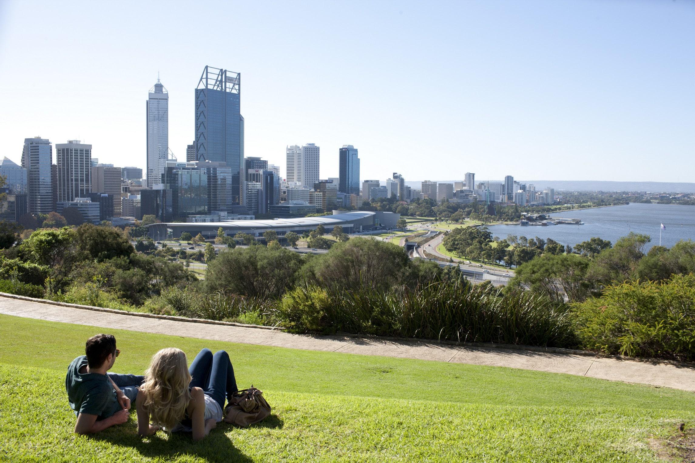 Un couple allongé sur l'herbe oberve le paysage urbain en Australie