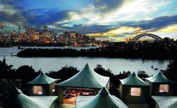 Paysage de tentes au bord du fleuve avec ville en arrière plan