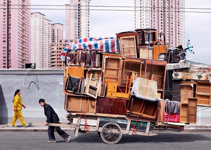 Un homme traîne une charrette remplie de meubles