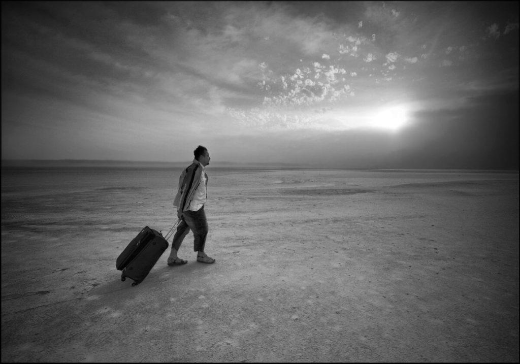 Un homme seul marche en tirant une valise